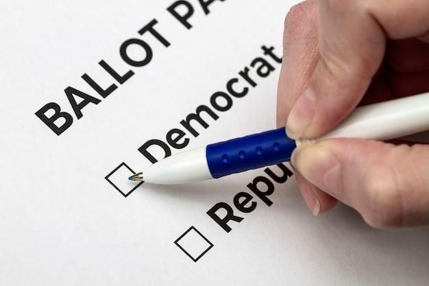 Wyborca przygotowuje się do głosowania na demokratę na karcie do głosowania