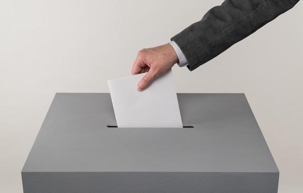 Wybory prezydenckie i parlamentarne wyborca wrzuca kartę do urny wyborczej