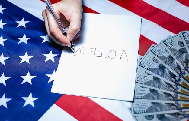 Wybory w usa. kobieta kładzie kleszcza na papierze do głosowania. zmiany polityczne w kraju. system korupcji. amerykańska flaga i pieniądze dolarów. ludzie głosujący w głosowaniu.