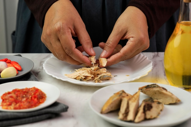 Wybrane focus kobieta home chef rozdrobnione gotowany tuńczyk makarel. przygotowanie do gotowania w kuchni przygotowanie tongkol suwir balado