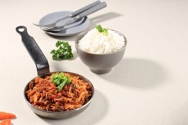 Wybrane focus pampis tongkol, tradycyjne danie manado z owoców morza z pikantnych rozdrobnionych ryb, podawane na żelaznej patelni z ryżem w ceramicznej misce. kopiuj przestrzeń