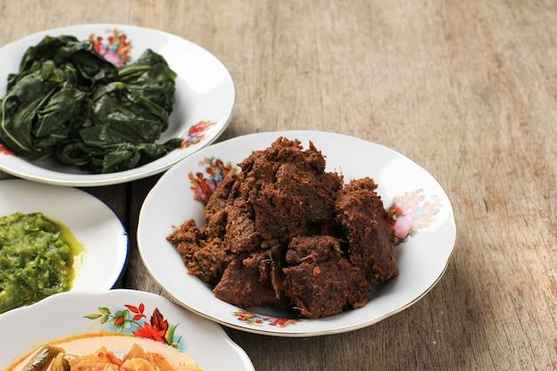 Wybrane focus rendang lub randang to najsmaczniejsze jedzenie na świecie. wykonane z gulaszu wołowego i mleka kokosowego z różnymi ziołami i sosem. zazwyczaj jedzenie z plemienia minang, west sumatera, indonezja