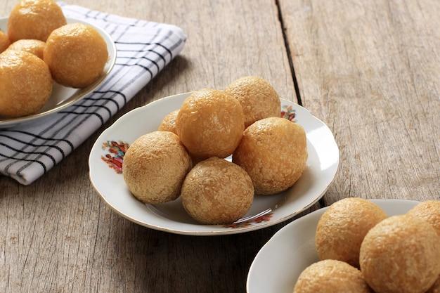 Wybrane focus top view tahu bulat (okrągłe tofu), ulubione danie indonezji, smażone w głębokim tłuszczu i doprawione przyprawą w proszku. skopiuj miejsce na tle drewna