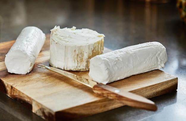Wybrane francuskie sery na desce z rozmarynem i nożem.