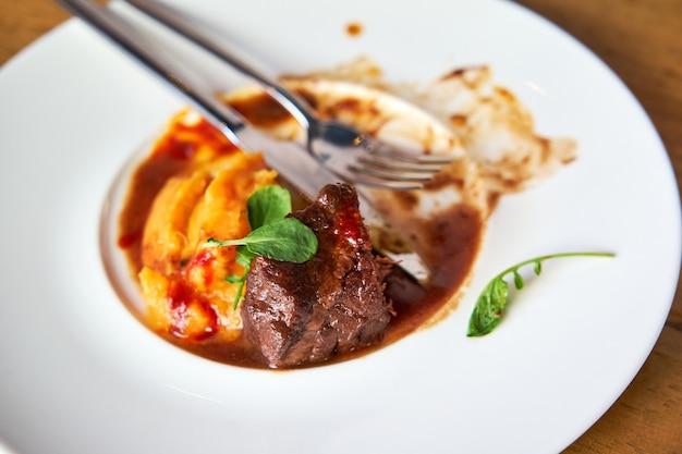 Wybrane skupienie na kawałku mięsa w talerzu z resztkami jedzenia i widelcami z policzkami cielęcymi z mojo kokosowym i puree z tuńczyka z sosem pomarańczowym podanym w białym talerzu ceramicznym na drewnianym stole