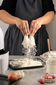 Wybrane skupienie na podudzie, kobieta kucharz robi domowy chrupiący kurczak smażony, panierowanie podudzi z kurczaka z mąką w kuchni, fotografia akcji