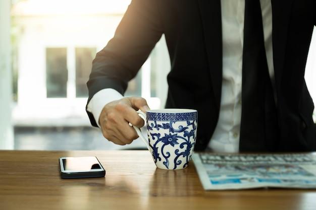 Wybrany ostrości kawowego kubka biznesmen ma kawę i czytający gazetę z telefonem komórkowym