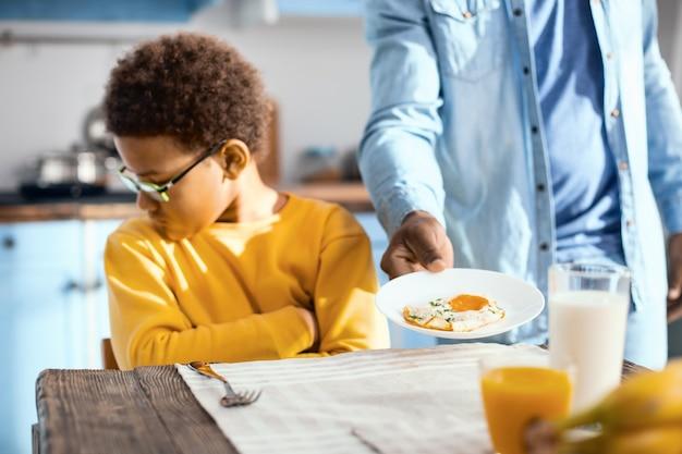 Wybredny. nadąsany chłopiec siedzący przy stole i odwracający się, odmawiając jedzenia smażonego jajka