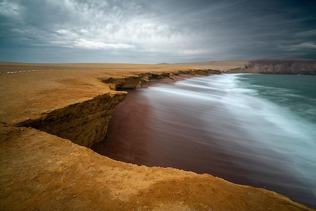 Wybrzeże i czerwona piaszczysta plaża rezerwatu narodowego paracas w peru in