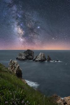Wybrzeże krajobraz z niektórych skał z morzem i nocnym niebem