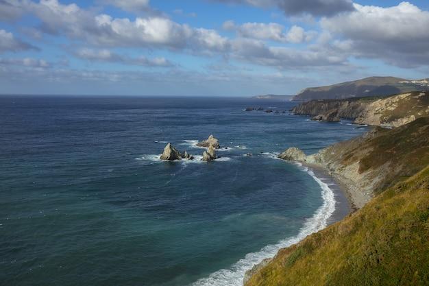 Wybrzeże loiba otoczone morzem pod zachmurzonym niebem w ciągu dnia w galicji w hiszpanii