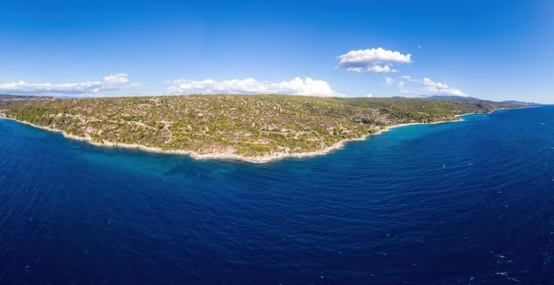 Wybrzeże morza egejskiego grecji, skaliste wzgórza porośnięte drzewami i krzewami, kilka budynków w pobliżu brzegu