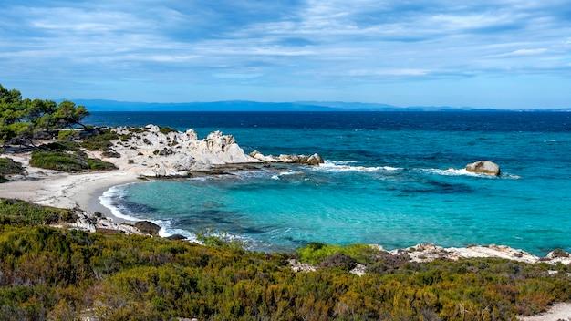 Wybrzeże morza egejskiego otoczone zielenią, skałami, krzewami i drzewami, błękitna woda z falami, grecja