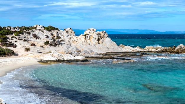 Wybrzeże morza egejskiego otoczone zielenią, skały i krzaki, błękitna woda z falami, grecja