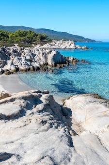 Wybrzeże morza egejskiego otoczone zielenią, skały, krzewy i drzewa, błękitna woda, grecja