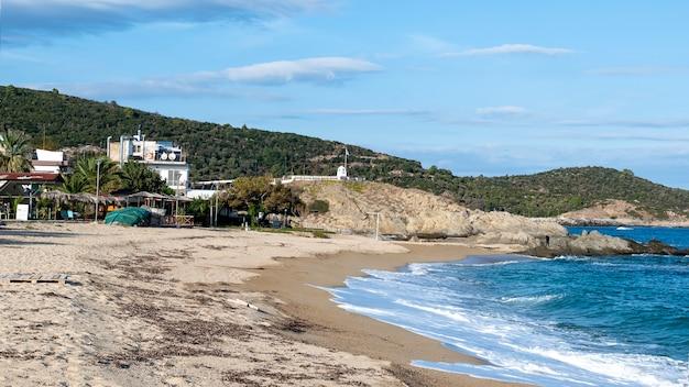 Wybrzeże morza egejskiego z budynkami po lewej stronie, skały, krzewy i drzewa, błękitna woda z falami w sarti, grecja