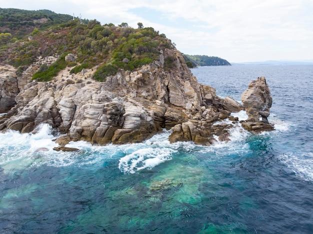 Wybrzeże morza egejskiego z niebieską przezroczystą wodą, falami, zielenią dookoła, skałami, krzewami i drzewami, widok z drona grecja