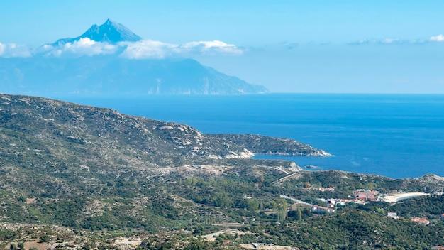 Wybrzeże morza egejskiego ze wzgórzami pełnymi zieleni, zabudowania w pobliżu wybrzeża z wysoką górą sięgającą chmur grecja