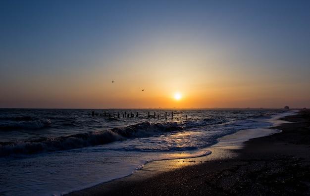 Wybrzeże morza o zachodzie słońca. fale morskie.