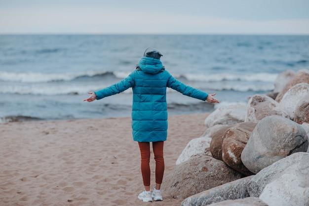 Wybrzeże morza z błękitną wodą. pogoda sztormowa na jeziorze. piaszczysta plaża przy złej pogodzie. kobieta na skałach na linii brzegowej.