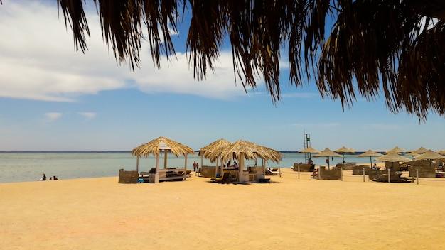 Wybrzeże morza z parasolami krytymi strzechą na piaszczystej plaży. seascape na plaży pod koniec sezonu wakacyjnego. świetne miejsce na relaks nad morzem czerwonym w sharm el sheikh w egipcie.