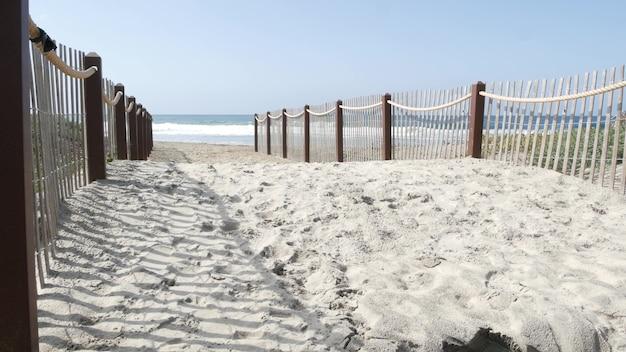 Wybrzeże oceanu, drewniany płot na brzegu morza. fale wody na plaży, kalifornia usa. dostęp do wybrzeża