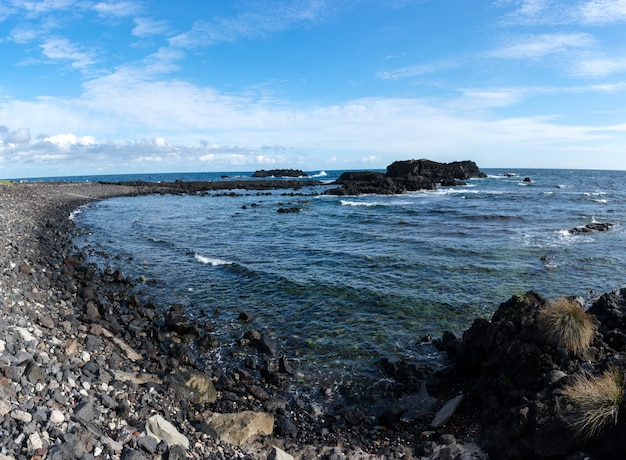 Wybrzeże skał na azorach. fale rozpryskujące się na skałach bazaltowych