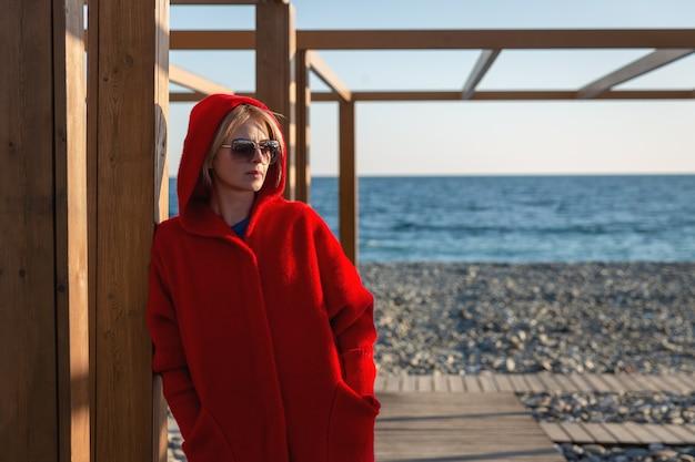 Wybrzeże w pogodny, słoneczny dzień. kobieta w czerwonym płaszczu i okularach przeciwsłonecznych opiera się o ścianę.