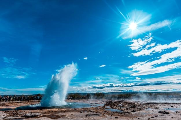 Wybuch wody w geysir strokkur ze słońcem w tle złotego kręgu na południu islandii