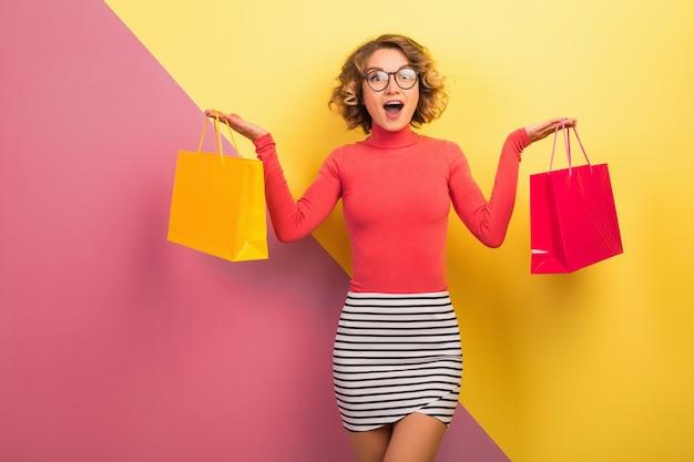 Wychodząca atrakcyjna kobieta w stylowym, kolorowym stroju trzymająca torby na zakupy z zaskoczonym wyrazem twarzy, zabawne emocje, różowe żółte tło, polo, mini spódniczka w paski, wyprzedaż, dyskoteka, zakupoholiczka