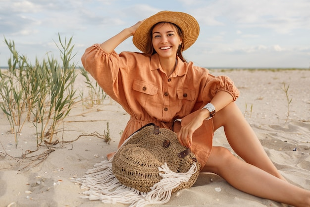 Wychodząca brunetka z idealnym uśmiechem, bawiąca się na słonecznej plaży, siedząca na białym piasku w pobliżu oceanu.