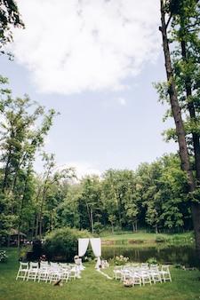 Wychodząca ceremonia ślubna. decor studio. białe drewniane krzesła na zielonym trawniku. łuk świąteczny. białe fotele dla gości