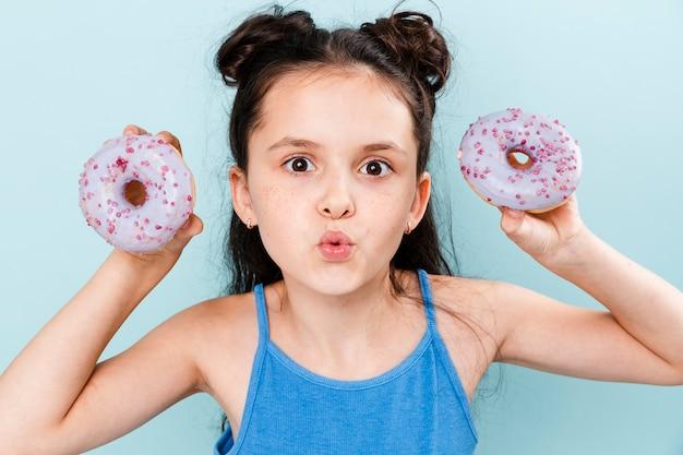 Wychodząca dziewczyna trzyma dwa pączki