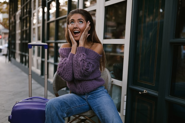 Wychodzący model z niebieską walizką siedzący na krześle w pobliżu kawiarni, w fioletowym swetrze, dżinsy, makijaż, uczesanie, emocje, zaskoczony, jesień, blondynka, szczęśliwa, dzianinowa, uśmiechnięta