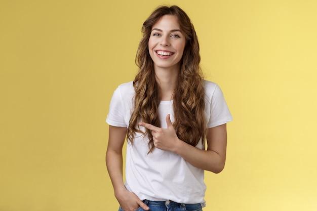 Wychodzący uroczy szczęśliwy ładna kobieta kręcone długie fryzury wskazujący palec wskazujący w lewo wskazują reklama śmiejąc się beztroski zadowolony trzymać kieszeń dorywczo przyjazny poza żółtym tle.