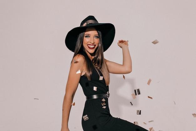 Wychodzi aktywna, śmiejąca się brunetka kobieta w czarnym kapeluszu i eleganckiej czarnej sukni z ciemnymi ustami, czekająca na imprezę