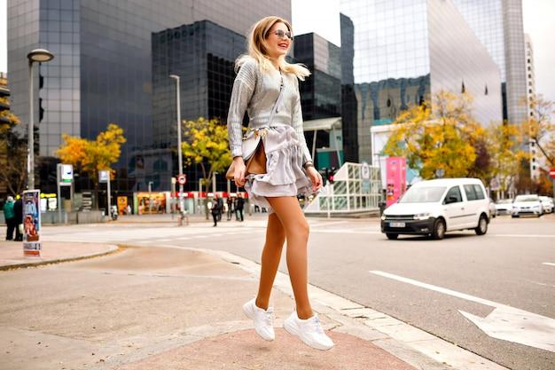 Wychodzi błoga blondynka skacząca, tańcząca i bawiąca się na ulicy w pobliżu nowoczesnego budynku, stylowe eleganckie srebrne trampki, luksusowa torba i okulary przeciwsłoneczne, szczęśliwa turystka w nowym jorku.