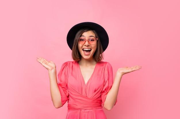 Wychodzi roześmiana kobieta w stylowym kapeluszu, pozowanie na różowej ścianie