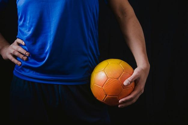 Wyciąć piłkarz trzymający piłkę