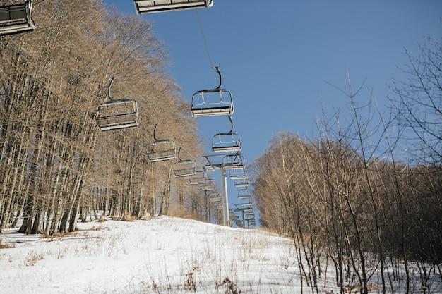 Wyciąg krzesełkowy na zaśnieżoną górę na tle błękitnego nieba we włoszech w zimie w słoneczny dzień