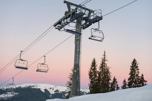 Wyciąg krzesełkowy w zimowym kurorcie na tle pięknego nieba o zachodzie słońca