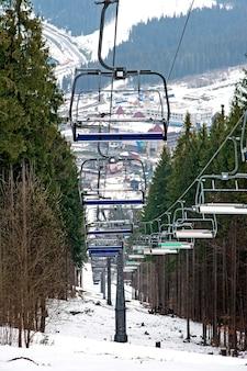 Wyciąg narciarski i trasa narciarska wśród lasu w ośrodku narciarskim w karpatach