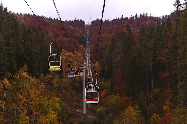Wyciąg narciarski w jesiennych górach wśród pięknych widoków z żółtymi i czerwonymi drzewami koncepcja wanderlust