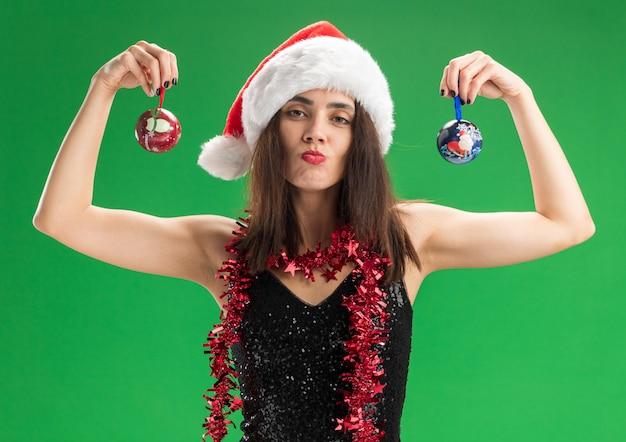 Wyciągając usta młoda piękna dziewczyna ubrana w świąteczny kapelusz z girlandą na szyi, trzymając kulki choinkowe na białym tle na zielonym tle