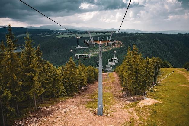 Wyciągi krzesełkowe otoczone wzgórzami pokrytymi zielenią pod zachmurzonym niebem