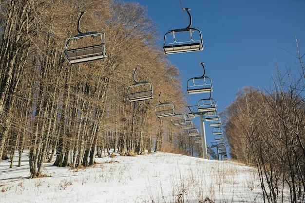 Wyciągi narciarskie w zaśnieżonej górze z błękitnym niebem w tle.