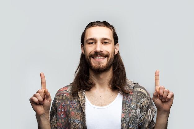 Wyciągnij palcami nad głowę uśmiechniętą twarzą, aby umieścić tekst, logo lub reklamę. modnisia podróżnika elegancki beztroski mężczyzna na białym pracownianym tle, ludzie stylów życia