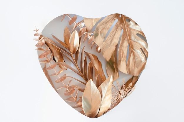 Wycięcie w kształcie serca ze złotymi liśćmi koncepcja miłości płaskie lay