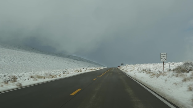Wycieczka do doliny śmierci, jazda samochodem, śnieg w kalifornii, usa. autostop zimą podróżując po ameryce. autostrada, przełęcz i sucha, jałowa dzicz. pov pasażera z samochodu. podróż do nevady.