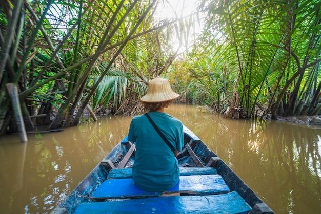 Wycieczka łódką po regionie delty mekongu, ben tre, wietnam południowy. turysta z wietnamskim kapeluszem na rejsie w wodnych kanałach